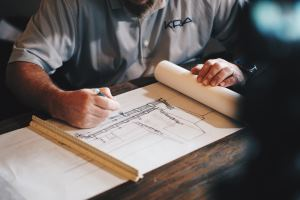 contractor / builder looks at house plans with handyman in hattiesburg